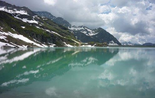 nowy mountain peaks reflect in the frigid water.